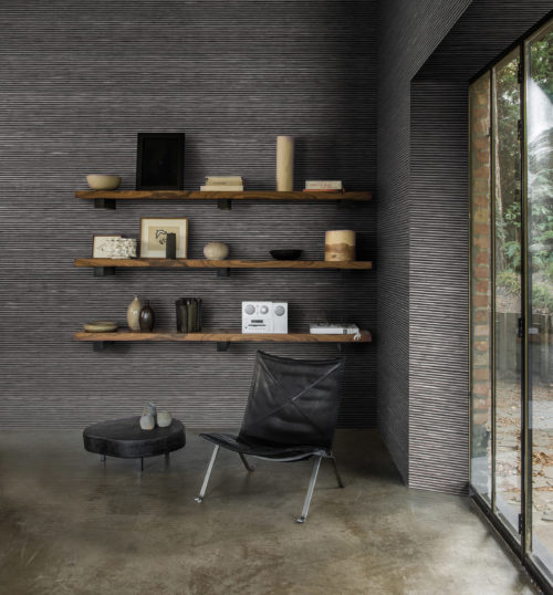 Contemporary straightforward interior with leather chair and huge window. The bicolour striped wallcovering in black and grey is installed horizontally, which makes the room bigger. On the wooden shelves on the wall we see a white Tivoli radio, vases and artworks.