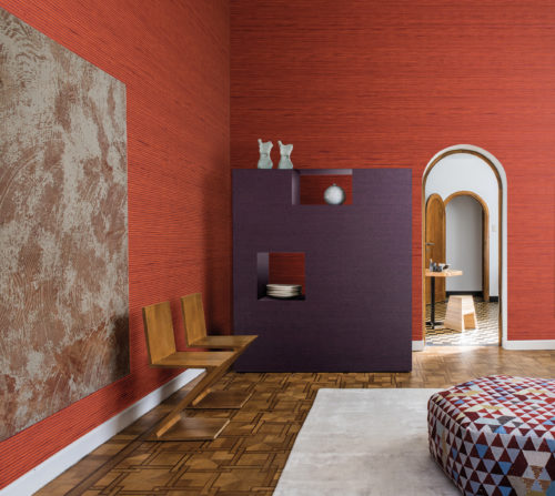 Impressive room: wooden inlay floors, hexagonal hassock with geometrical print, rounded doors. On the wall two vibrant Koyori wallcoverings in orange and purple.