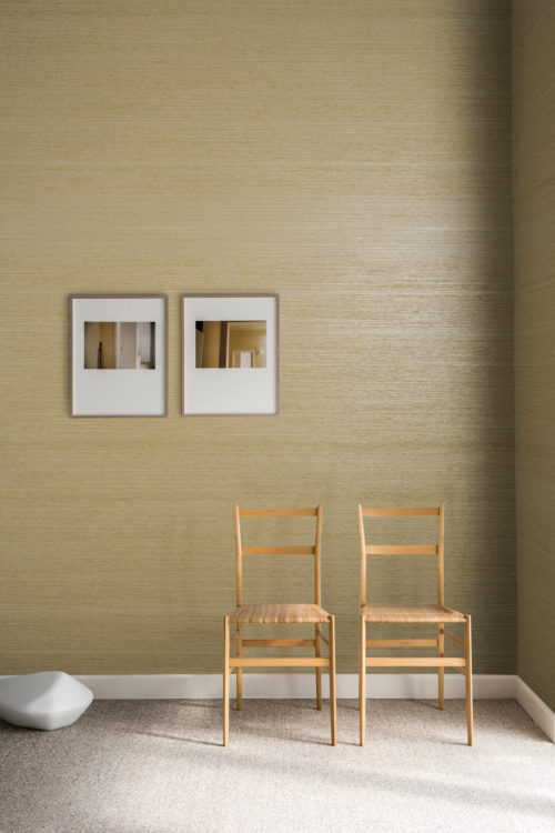 Assymetrical symmetry in this picture of two of the same chairs but two different artworks. On the floor a marble stone. On the wall a soft yellow Koyori wallcovering with a subtle pearlescent shimmer.