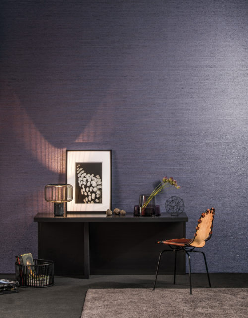 A desk in a tactile room with night blue wallcovering from the Omexco Koyori range. The a subtle pearlescent shimmer is brought out by the lamp with metal wires. More metal wires in the artwork on the desk.