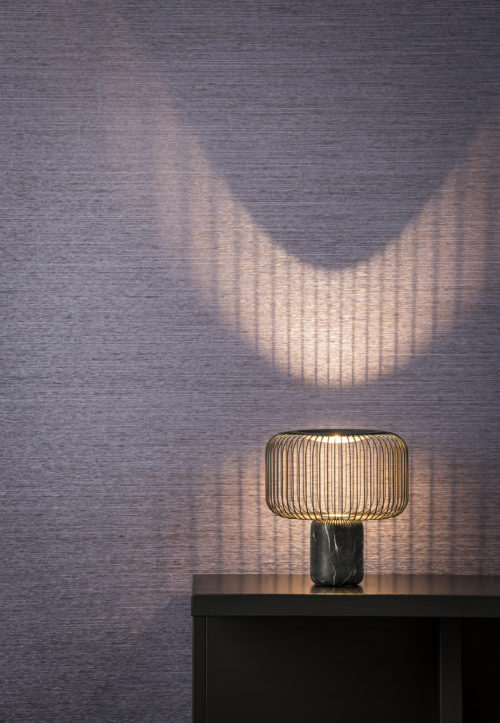 A console in a tactile room with night blue wallcovering from the Omexco Koyori range. The a subtle pearlescent shimmer is brought out by the lamp with metal wires.