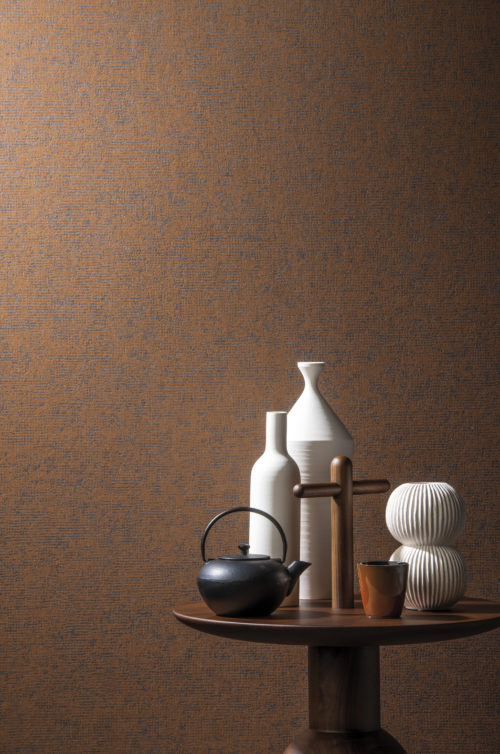 Nice contrast between the rust coloured non-woven wallcovering and accessories on a little wooden table with cross shaped handle: matt white vases, a japanese tea pot.