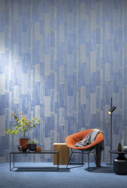 Impressive geometrical motif in electric blue from the Omexco Loft collection. The wallcovering is installed vertically and combined with a orange lounge chair and japanese maple plant.