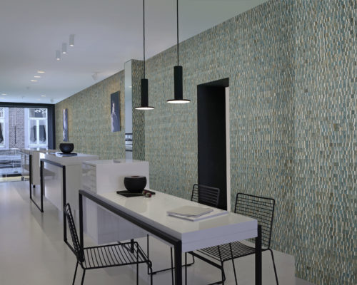 Impressive contemporary show with a white, high white counter. Black wire stools. Black metal lamps, black metal in the door opening. Turquoise stunning waterlily wallcovering from the Omexco Nomad range.