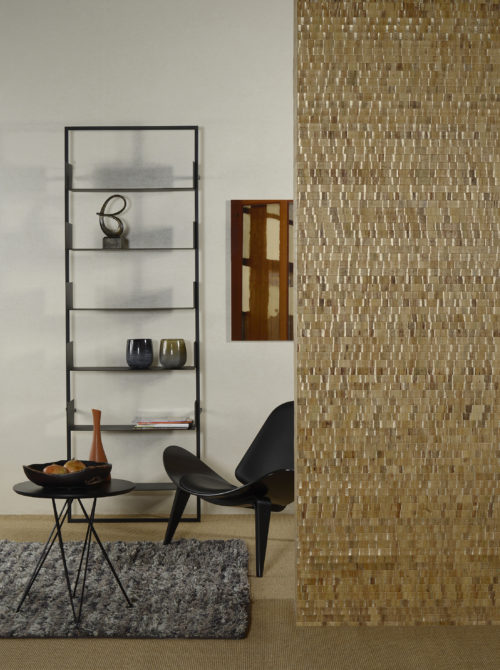 Omexco Nomad: waterlily leaves are woven in lively and generous colours. A detail of the yellow gold in this picture. It is combined with a non-woven wallcovering from the same collection. Black lounge chair and black shelves on the wall.
