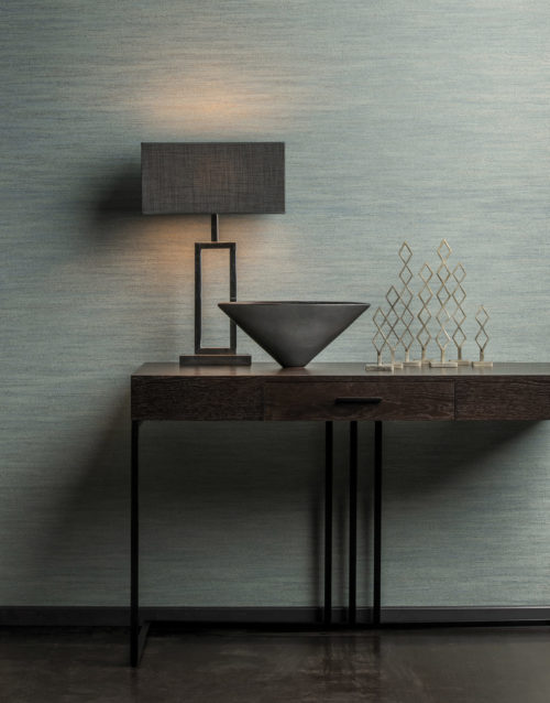 Green Omexco wallcovering, installed horizontally. In front of it a table lamp with grey shade on a desk with one drawer and black feet. Metal artwork with diamond shapes.