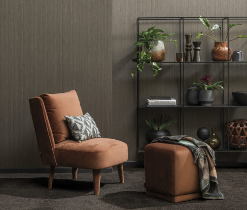 Detail of a brown wall with horizontally installed wallcoverings by Omexco. In front of it an orange velvet armchair and square stool. In the background a metal rack with vases and books.