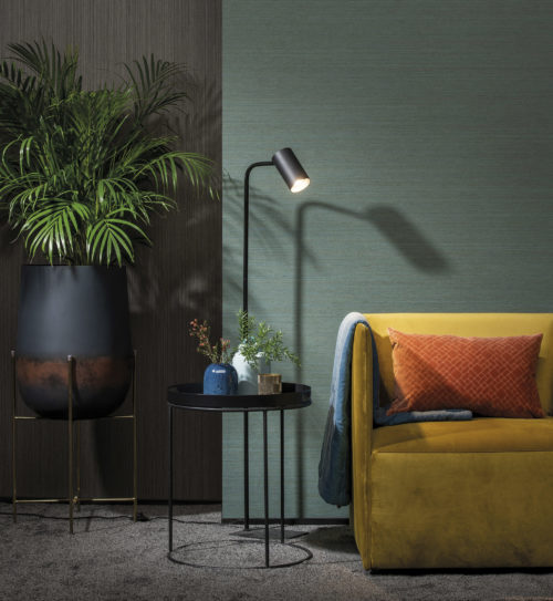 Decor with yellow velvet armchair, floor lamp, metal table. On the left a vase on handcrafted aluminium on iron statue.