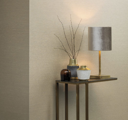 Cream coloured wallcovering, shown horizontally. Metal end table with a gold look. On the table vases with white and grey pearls. Table lamp with metallic shine.