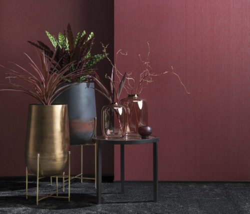 Little group of vases, 3 on an end table with marble top, two on a handcrafted iron statue. Behind it burgundy Portfolio wallcoverings by Omexco.