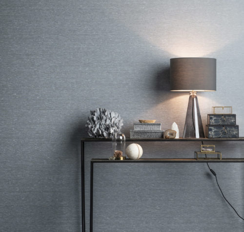 Two console tables in metal. On them light blue and grey accessories. Square glass boxes. Behind it Portfolio wallcoverings. Grey lamp gives a pink hint to the whole.