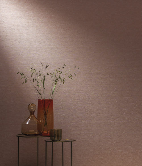 Pink Omexco wallcoverings, shown horizontally. Tables with iron base and antique finished mirror. Red vase with springy plants.