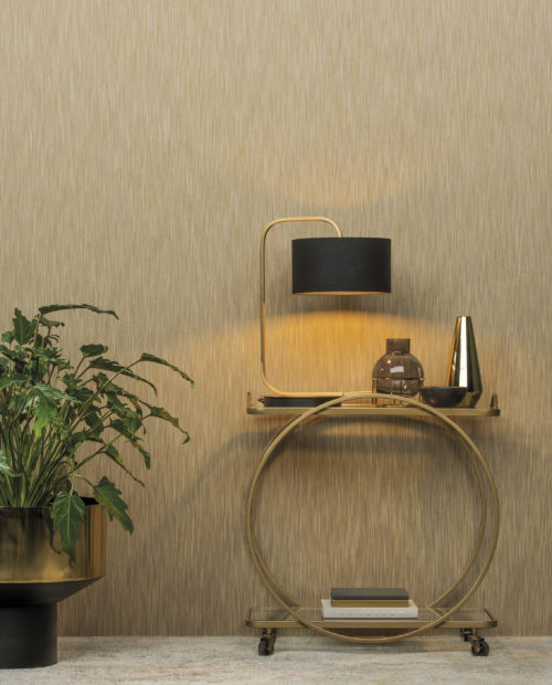 Golden table with golden lamp and black shade. Iron vase. Behind it ikat yarns wallcoverings by Omexco.