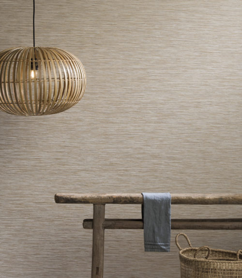 Wall dressed with Omexco Portfolio wallcovering, antique wooden side table, rotan lamp, basket.