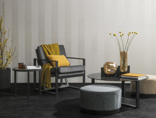 Picture of a wall with linnen Omexco wallcoverings. Iron frame table, side table and lounge chair. Yellow details.