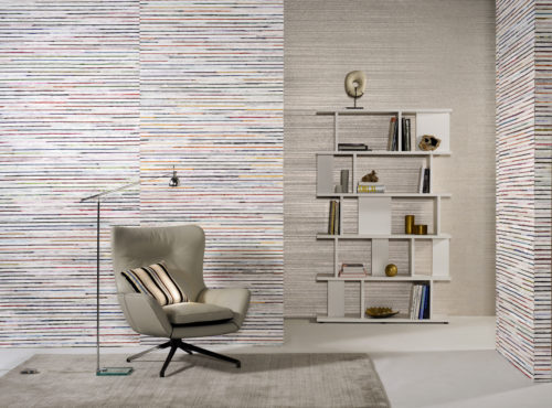 A peacefull room with earth tones: grey plain wallcovering with foil on the far wall. A modern bookshelf brings the room to life. Natural bakbak and recycled sari silk wallcovering on the other walls. Inviting lounge chair and reading light.