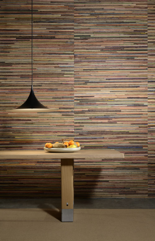 The explosion of colours of recycled sari silk, woven with strips of bakbak is at the origin of the name of this top-notch wallcovering collection Rainbows by Omexco. It bringts to life this interior with black lamp, wooden table and bowl of fresh fruit.