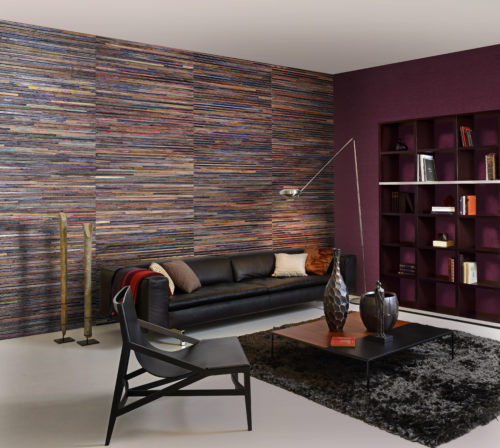 The explosion of colours of recycled sari silk, woven with strips of bakbak (bark of the banana tree) is at the origin of the name of this top-notch wallcovering collection. Each metre of this product is unique, since the colours of the silk alternate, without ever being repeated. The bakbak is coloured in chalk white, cinnamon or chestnut – three different atmospheres to illuminate, soften or intensify the rainbow of the silk fabric. In this picture the chestnut is used in a tactile living room with warm colours and ethnic details.