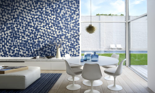 Modern room with retro white furniture. . Squares of crushed paper on the wall in electric blue and white.