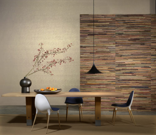 The explosion of colours of recycled sari silk, woven with strips of bakbak (bark of the banana tree) is at the origin of the name of this top-notch wallcovering collection. Each metre of this product is unique, since the colours of the silk alternate, without ever being repeated. The bakbak is coloured in chalk white, cinnamon or chestnut – three different atmospheres to illuminate, soften or intensify the rainbow of the silk fabric. In this dining room we see the cinnamon colour alternated with a plain wallcovering from the same range in light brown and gold foil.
