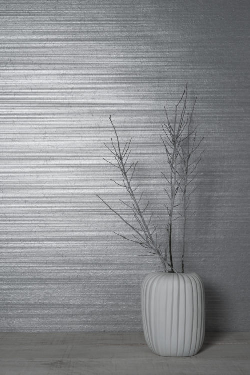 This elegant plain wallcovering from the Omexco Rainbows range exists in many colours. This light grey plain is enhanced by applying lines of silver foil. The silver branch in the vase brings out the colour beautifully. A little sisal thread provides some texture.