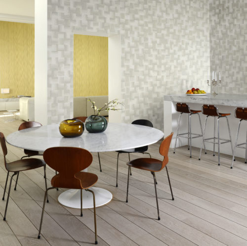 The Omexco Rainbows collection: squares of crushed paper, printed in faded shades and glued on a non-woven backing bring in perfect harmony in this dining room with white marble table tops. The living room in the back is decorated in contrasting yellow RAA405 from the same range.