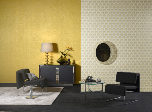Like the gardens of Shalimar, near Lahore (Pakistan), the wallcovering collection Shalimar of Omexco took inspiration from the fusion of arab and persian influences. This beautiful motif was printed on rayon warps for a luxurious feel. The curcuma yellow of the moiré is stunning. We see a black leather lounge chair and glass decorator mirror.