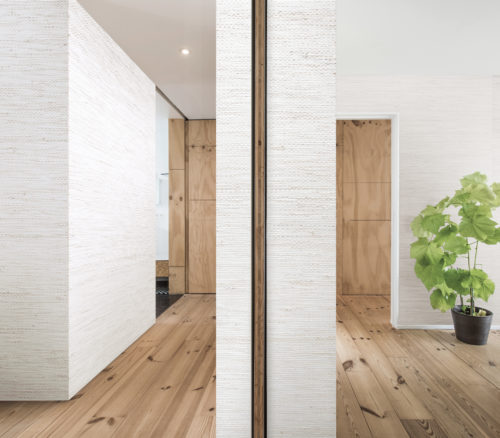 Room with wooden floors. The room is devided in two by a wall. On both sides of he wall bacnoc and paper weave wallcovering. It gives the bland room a lot of life. On the far right wall:  jute weave wallcovering.