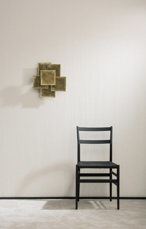 A lone black chair stands next to an art piece that unfolds on the wall. Crushed linnen Omexco wallcovering.