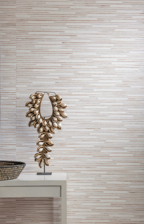 Detail of waterlily and paper weave wallcovering in white and nude tones. Artwork with shells on a white console.