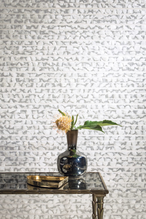 A dark glass table reflecting grey and white capiz wallcovering from the Shades of Pale collection.