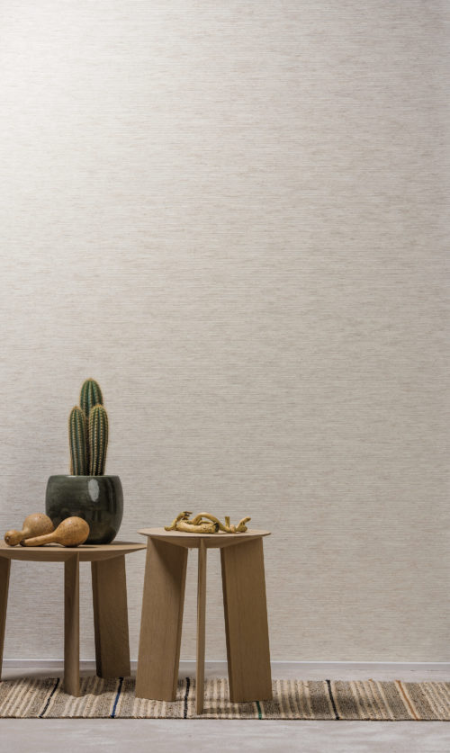 Two wooden stools: one with a cactus and maracas, one with pieces of washed wood. Linen woven wallcovering on the wall.