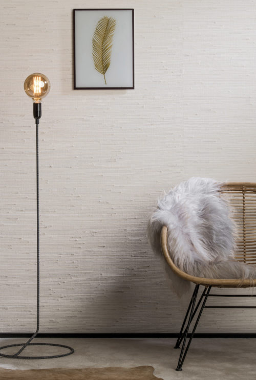 Cosy detail of jute and grass wallcovering on the wall. Chair with fluffy animal skin. Feather artwork on the wall.
