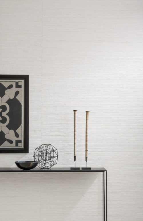 Detail of white wallcovering with jute weave. Black accessories in contrast: artwork, bowl, candles.