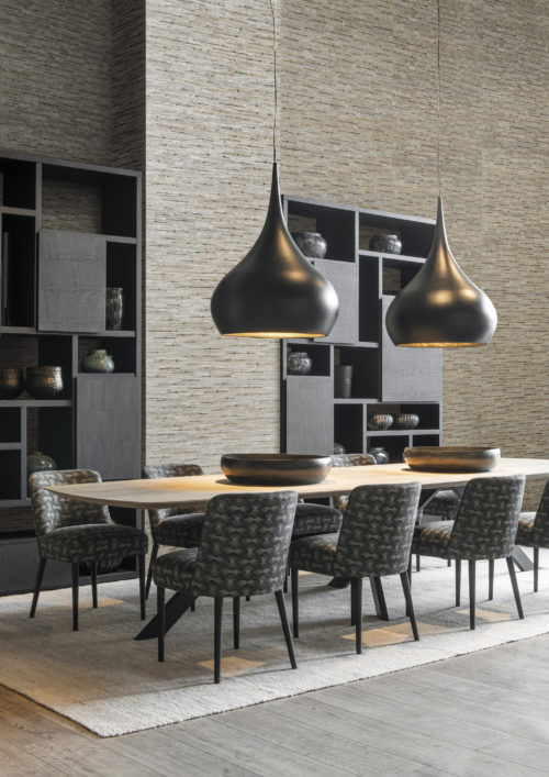 If we desire an interior space that honours our authentic personality and becomes a personal sanctuary providing peace and wellbeing, Seraya is our natural choice... In this picture we see a dining room with black cabinets. On the walls: woven rattan & bacnoc, a unison of two fibres - the bacnoc knots are intertwined with the rippled rattan fibres - creating a perfect decorative harmony.