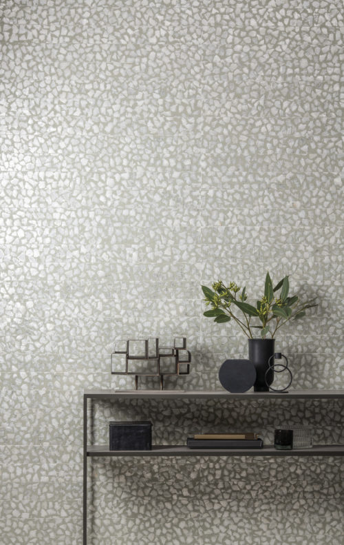 We've created a little world here: our capiz mother of pearl wallcovering on the wall. A metal console with books, a little artwork and some plants. Our mother of pearl is unique and precious. Natural capiz flakes are laminated onto a non woven backing to form a mosaic, then cut into ribbons and woven by hand: Omexco Seraya at it's best.