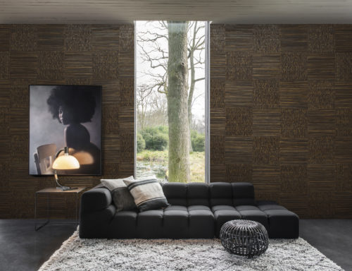 Living room with a anthracite lounge chair, lush carpet and round pouf. On the wall a picture of a girl with an afro. The walls are dressed in woven banana bark: the elegance of this natural material arises from the intricate craftsmanship of an experienced artisan who collects the banana bark from tropical climes. The Omexco Seraya collection.