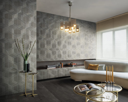 On the walls of this living room: the cubist design in taupe from Omexco's Sycamore collection. It's a wood veneer wallcovering with a geometrical interlocked pattern. The wallcovering is paired with a beige sofa, golden retro glass lamp, yellow pillow, yellow candles and golden side tables.