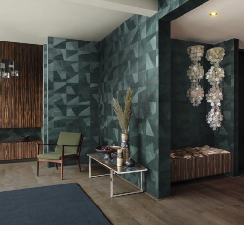 We see a stunning room with retro furniture and lamps. The perfect backdrop for the warm green and chic interlocking wood textures of the Dimensions design of the Omexco Sycamore collection.