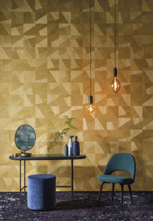 In this picture an example of how the Omexco Sycamore collection embodies natural beauty and soft glamour. A beautiful contrast between the yellow dimensions design of chic interlocking wood textures with green interior details: a chair, pouf, pendulum lights and in the mirror we see the same wallcovering in green appear.