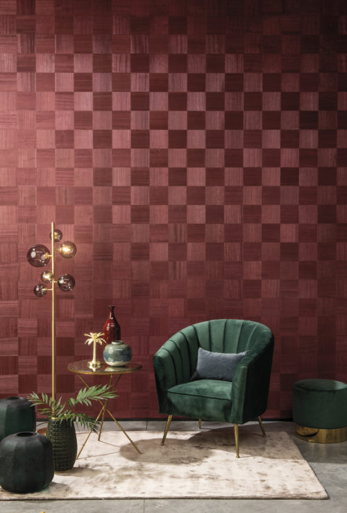 Did the Queen's Gambit inspire Omexco to make this exclusive wallcovering called 'Chess': soft glamour, subtle harmony? In this picture the red design of exquisite wood inlay is combined with a contrasting green velvet chair and gold interior details.