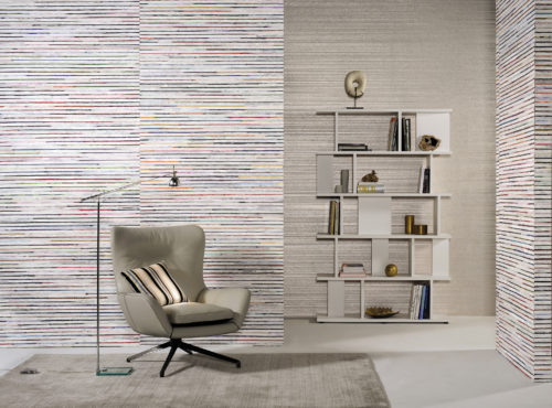 A peacefull room with earth tones: grey plain wallcovering with foil on the far wall. A modern bookshelf brings the room to life. Natural bakbak and recycled sari silk Seraya wallcovering on the other walls. Inviting lounge chair and reading light.