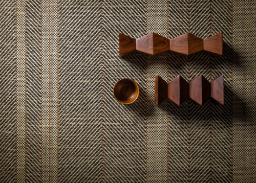 A closeup of Omexco's paperweave collection Tribu. The design we see here is a stunning rhythmic stripe. Wooden decorative elements were added to create an interesting setting.