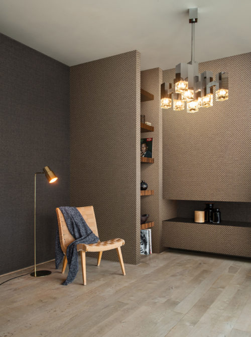The Tribu collection by Omexco satisfies your desire for multicultural modernism and timeless design. In this image, we see a modern living room nook with a lounge chair and strikingly modern paperweave wallcoverings in earthy shades.