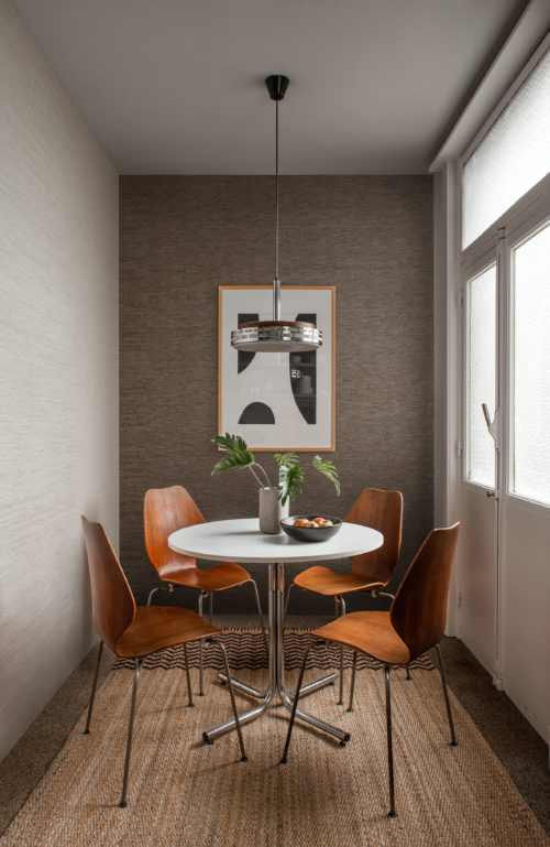 In this image we see a cosy dining nook with a vintage round dining table and retro wooden chairs, a pendulum lamp and ethnic woven carpet. On the walls, we see beige and brown paper yarns delicately woven into seamless wallcoverings by Omexco. Design 'Flow' from the wallcovering collection Tribu.