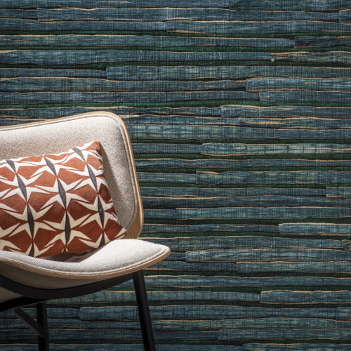 Outstanding waterlily wallcovering in dark green. In front of it a white chair with orange geometric pillow.