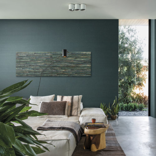 Green interior of a bedroom with concrete floor. Bed with assorted pillows, close to the floor. Aruba wallcovering on the wall. On the wall an artwork of the waterlily from the same wallcovering collection.