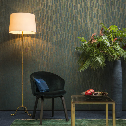 Picture with green interior. Tall vase with tropical plant, golden lamp and centre table. Night blue velvet chair. Green carpet. Art deco wallcovering in green and gold completes the whole.