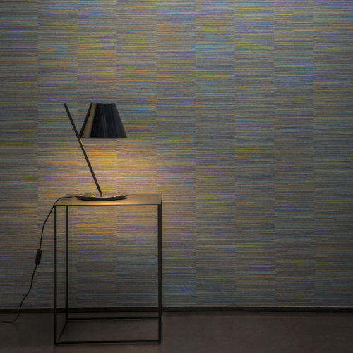 Detail of a blue Avenue wallcovering with short horizontal stripes. A little black lamp shines on the wall and a black table.