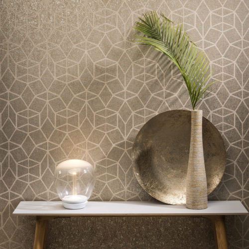 Wooden table, on the table a vase with a palm leaf. Glass orb light. Gold foil art deco wallcovering on the wall.